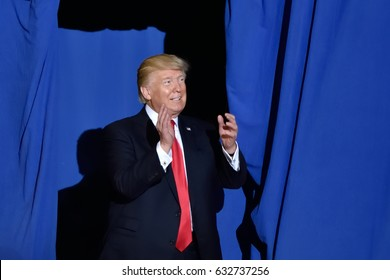 HARRISBURG, PA - APRIL 29, 2017: President Donald Trump enters the stage to applause before giving a speech marking 100 days in office. Held at The Farm Show Complex and Expo Center.