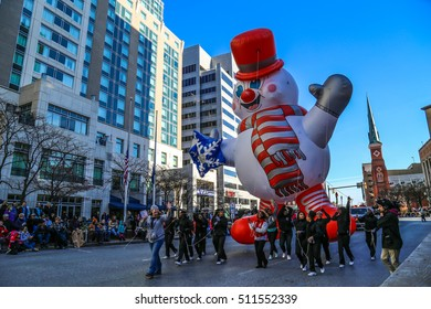 Harrisburg, PA - November 21, 2015: A large frosty snowman balloon proceeding on the downtown street in the annual Holiday Parade.
