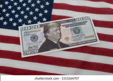 Harrisburg, PA - September 26, 2019 : Donald Trump 2020 Re-Election Presidential Dollar Bill against a United States of America flag.