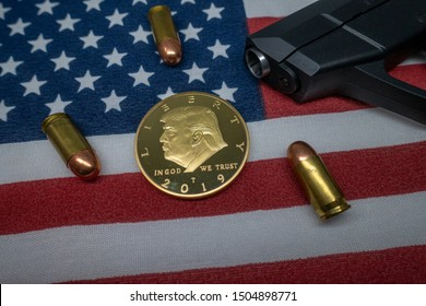 Harrisburg, PA - September 6, 2019 : Donald Trump coin against a United States of America flag surrounded by a fire arm and ammunition.