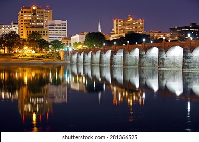 Harrisburg, Pennsylvania and the historic Market Street Bridge reflected on the Susquehanna River at night.