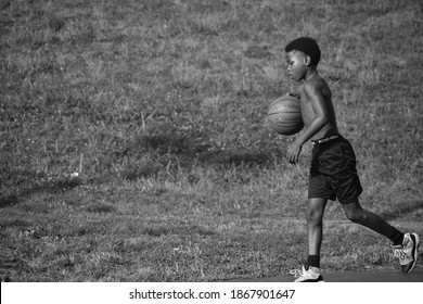 Harrisburg, Pennsylvania United States of America - August 5th, 2019: inner-city youth dribbles basketball for practice in a summer youth program