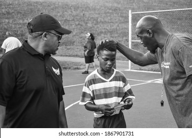 Harrisburg, Pennsylvania United States of America - July 10th 2019: Two Volunteering coaches motivate an inner-city youth after a tough basketball game