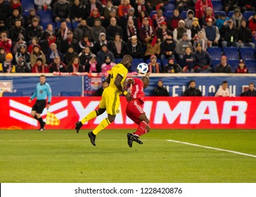 Harrison NJ - Nov 11 2018: Bradley Wright_Phillips (99) of Red Bulls & Jonathan Mensah (4) of Columbus Crew SC fight for ball during 2nd leg MLS Cup Eastern Conference semifinal game at Red Bull Arena
