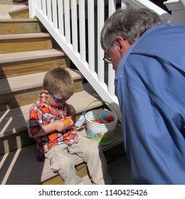 "Harrisonburg, VA, USA - 4/8/2012: a boy shows his Easter hunt ""loot"" to his uncle"