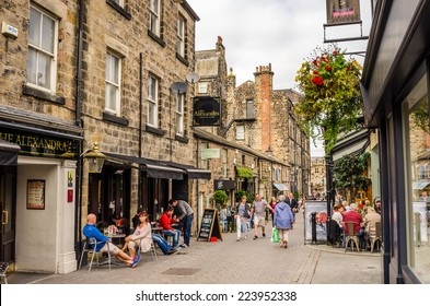 Harrogate, UK - September 27, 2014: People enjoying a warm Autumn day in a cobbled Street lined with Restaurant and Shops. Harrogate is consistently voted as one of the best places to live in the UK.