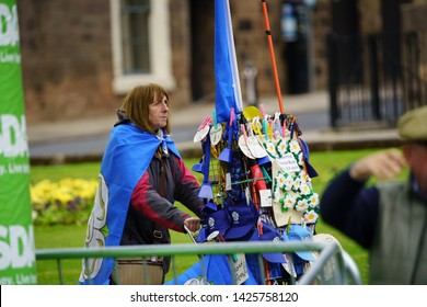Harrogate,North Yorkshire,England.5.3.2019.Woman selling Yorkshire flags,white roses,and caps from a trolley near the sprint finish on the first stage of the men's Tour de Yorkshire in town centre.