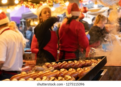 Harrogate,North Yorkshire,United Kingdom.11.17.2018.Large Sausages sizzling on a steel tray at a Christmas Market.