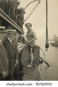 Harry Houdini stepping into a crate to be lowered into New York Harbor on July 7, 1912. In this stunts public debut, Houdini was locked in handcuffs and leg-irons, then nailed into the crate weighed d