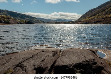 Harsh rocky landscape with lake full of water. Amazing scenery, very peaceful and remote. Gorgeous spring day with blue skies and sun shining.