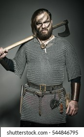 Harsh viking with axe on his shoulder after the battle