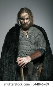 Harsh viking in furs stands and looking in camera
