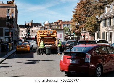 HARVARD, MA, USA - CIRCA OCTOBER 2016: Waste collection truck seen collecting bins in a busy street with garbage men seen at the rear of the truck.