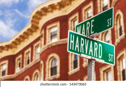 Harvard street sign with a classic red brick building in the background . Location: Harvard University in Cambridge, Massachusetts, USA.