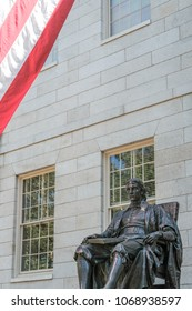 Harvard University, Harvard, USA - Circa September 2016: Isolated sculpture of founder of Harvard University, John Harvard, seen outside the main hall with part of a US flag in the frame.