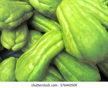 Harvest in Asia. Chayote (Sechium edule, Mexican cucumber, vegetable pear) scattered evenly, bazaar. Background