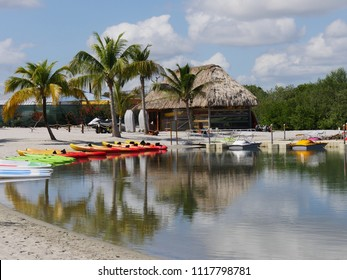 HARVEST CAYE, BELIZE—JANUARY 2018: Colorful kayaks and paddle boards infront of a covered hut at a lagoon in Harvest Caye.