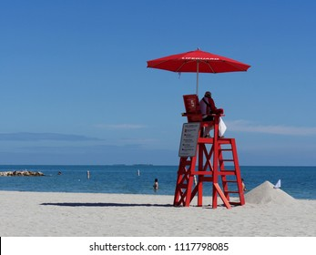 HARVEST CAYE, BELIZE—JANUARY 2018: A lifeguard sits on top of a high chair with a red umbrella at the Harvest Caye beach.