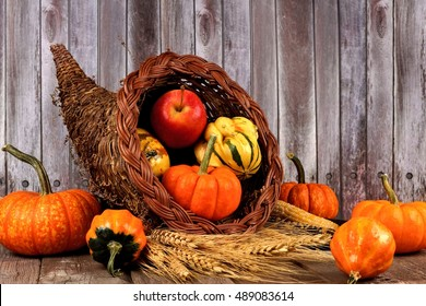 Harvest cornucopia with pumpkins, apples and gourds on rustic wood background