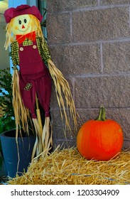 Harvest display with scarecrow and hay bales. Thanksgiving, harvest and autumn decoration. Scarecrow and bail of hay in USA.