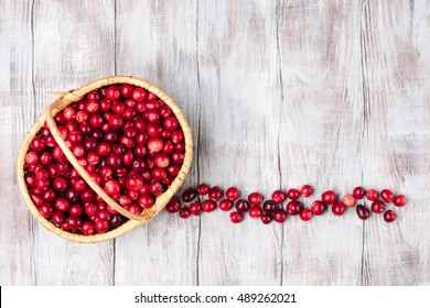 Harvest fresh red cranberries in wicker basket on rustic white wooden background, Top view. Autumn concept
