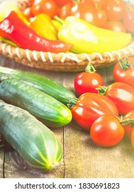 Harvest of fresh ripe vegetables on wooden table and in rod bowl - pepper, tomato, cucumber. Healthy organic food, summer vitamins, BIO viands, natural background.