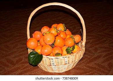 Harvest of orange persimmon fruit in a basket.