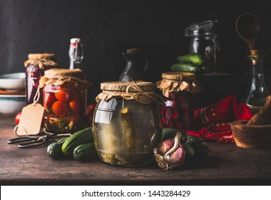 Harvest preserve concept. Glass jars with fermented, pickled and canned vegetables and fruits on dark rustic kitchen table. Conservation of farm organic seasonal harvest. Healthy homemade food