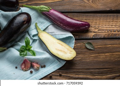Harvest - ripe juicy eggplant. Eggplants blue towel with leaves of basil, garlic. The cut aubergine lies on a wooden kitchen background.