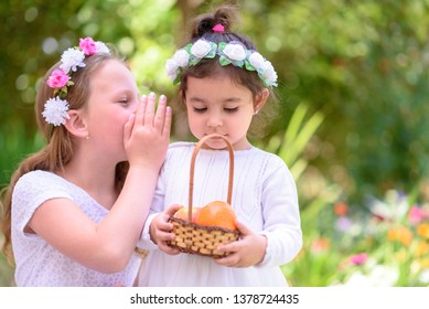 Harvest. Shavuot. Cute teenager girl with flower wreath whispering a secret to her little sister. Portrait adorable small kids outdoor.