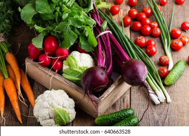 Harvest still life. Food composition of fresh organic vegetables, beets and carrots, cauliflower and radishes on rustic wooden table
