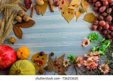 Harvest and Thanksgiving background with pomegranate, melon, mandarin, cinnamon sticks, wheat, flowers, walnuts and autumn leaves