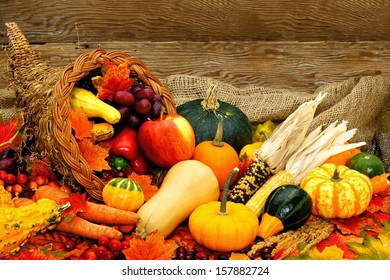 Harvest or Thanksgiving cornucopia filled with vegetables against wood background