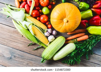 The harvest of vegetables. Vegetables (carrots, corn, cucumbers, tomatoes, onions, garlic, corn, pepper and others) are laid out on a wooden background. Studio photography. Healthy and natural food.