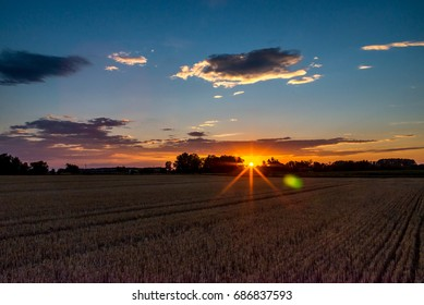 Harvested grain field on countryside at sunset