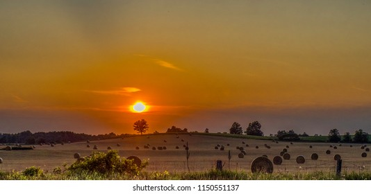 Harvested hay in bales at colourful sunset