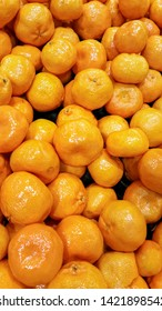 Harvested mandarins piled up for sale in a local fruit store. These citrus fruits are a good natural source of daily Vitamin C to support health.