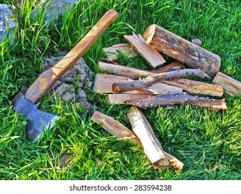 Harvested wood with axe lying on green grass