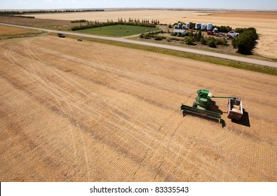 A harvester filling a grain truck with farm yard in background
