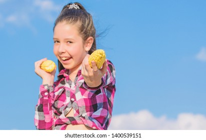 Harvesting and fun. Kids love corn food. Corn vegetarian and healthy organic product. Vegetarian nutrition concept. Kid girl hold yellow corn cob on sky background. Girl cheerful hold ripe corns.