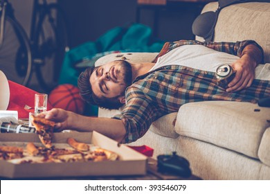 It has been a long night. Young handsome man passed out on sofa with pizza slice and beer can in his hand in messy room after party