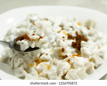 "It has served in white plate, Turkish ravioli ""manti"" dish made with dough"