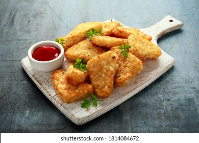 Hash brown potato with ketchup on white wooden board