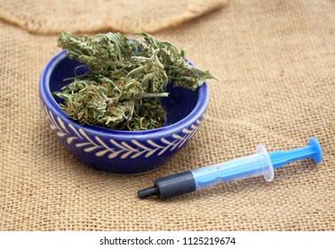 Hash oil phoenix tears medicine in little syringe with dry marijuana buds