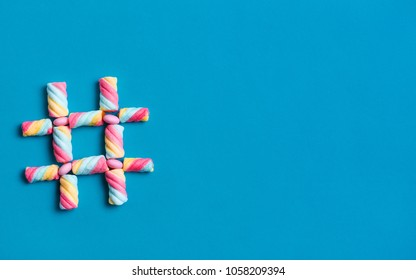Hash tag symbol made from sweets isolated on blue background with copy space for text.