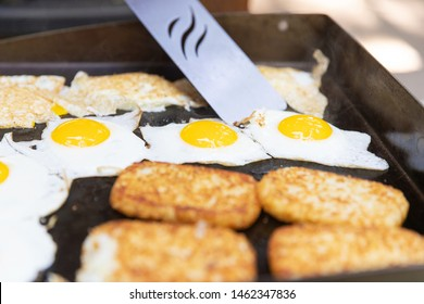 Hashbrowns and eggs cooked on a flat grill