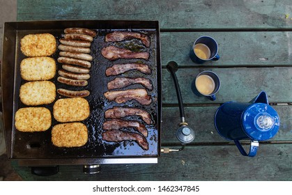 Hashbrowns, sausage, bacon cooking on a hot grill for breakfast with fresh pot of coffee on table