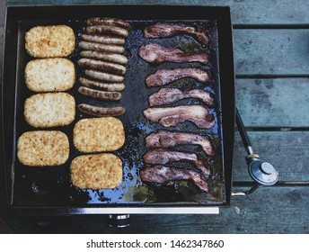 Hashbrowns, sausage, bacon cooking on a hot grill for breakfast