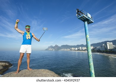 Hashtag gold medal athlete posing for a picture with his mobile phone on a selfie stick at Arpoador, Ipanema Beach in Rio de Janeiro, Brazil