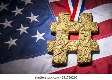 Hashtag gold medal rests on the red, white, and blue textured stars and stripes of an American flag